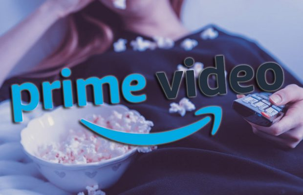 ragazza sdraiata sul letto che guarda serie tv in streaming su amazon prime video e mangia pop corn